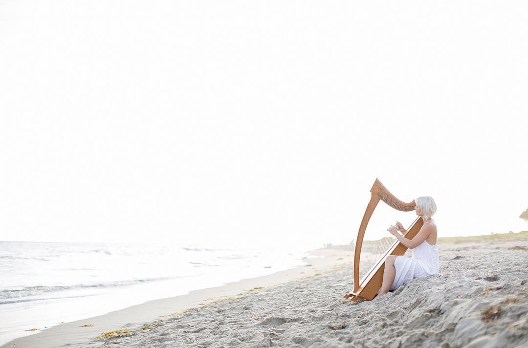 Woman playing harp on beach