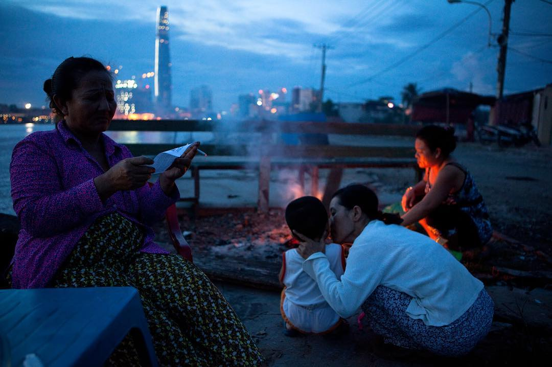 "Truong Thi Tuyet Hong reads the days lottery numbers while her grandson, Nguyen Tuan Minh Dat, ""Ben"", 3 years old, receives a kiss from the neighbor and his mother builds a fire at the end of the day. The fire is where the family spends their evening together as it wards off disease spreading mosquitos. Photo by John Thomas Rose"